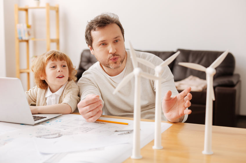 Father and child playing with wind turbine models